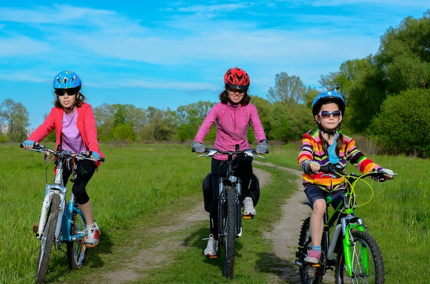 Feliz madre e hijos en bicicleta ciclismo al aire libre, deporte familiar activo