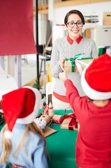 Feliz madre e hijos intercambiando regalos de navidad
