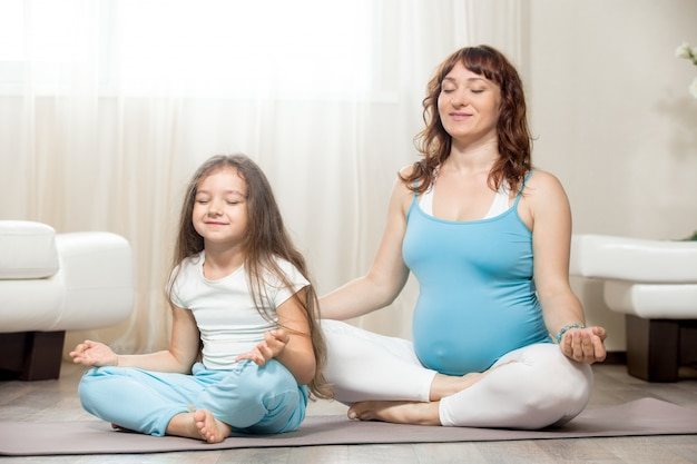 Feliz madre embarazada y niño meditando juntos en casa