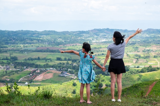 Feliz madre de familia asiática y su hija de pie en la cima de la hermosa montaña con las manos levantadas