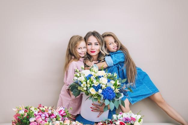 Feliz madre de familia y dos hijas de hermosas niñas de vacaciones en flores juntos