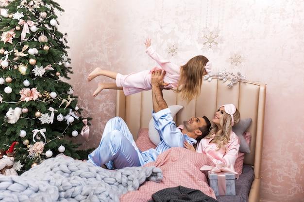 Feliz madre de familia, padre e hijo en la mañana de navidad en la cama en pijama