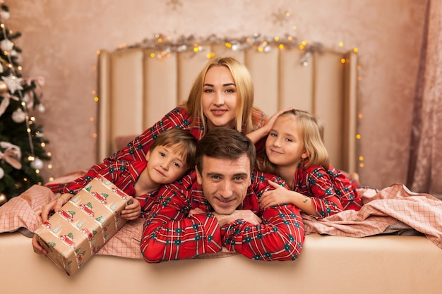 Feliz madre de familia, padre e hijos en la mañana de navidad en la cama en pijama