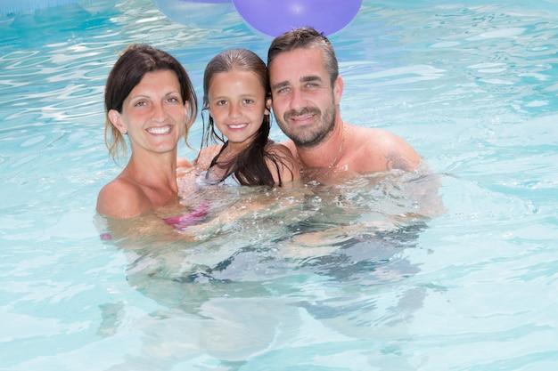 Feliz madre de familia y padre con hija en retrato de piscina de vacaciones
