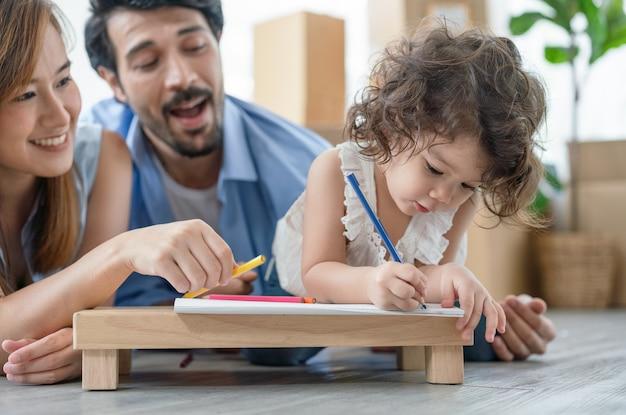 Feliz madre de familia y padre tirado en el suelo enseñando a su hija a dibujar en un libro a color juntos en la sala de estar en casa