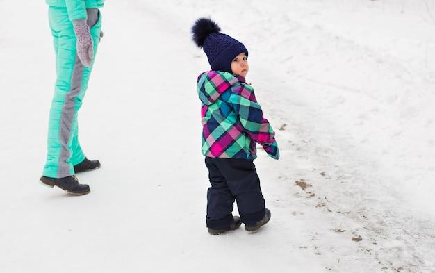 Feliz madre de familia y su hija bebé en un paseo de invierno en el bosque