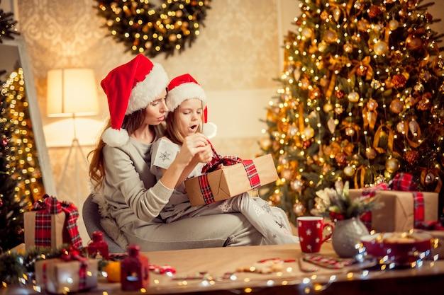 Una feliz madre de familia y su hijo empacan regalos de navidad