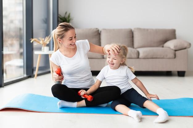 Feliz madre con hija en estera de yoga en casa