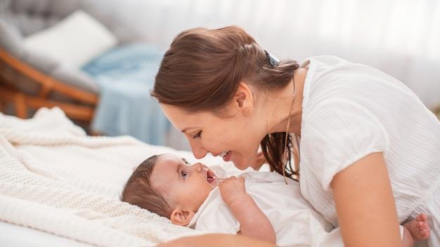 Feliz madre joven amorosa juega con su hijo