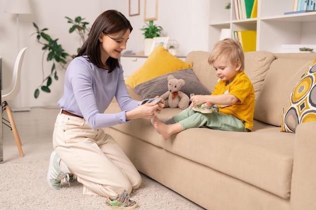 Feliz madre joven y cuidadosa de pie de rodillas y poniendo nuevos calcetines limpios en los pies de su pequeño y lindo hijo sentado en el sofá en el hogar.