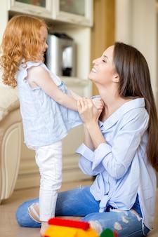 Feliz madre joven jugando con la hija pequeña