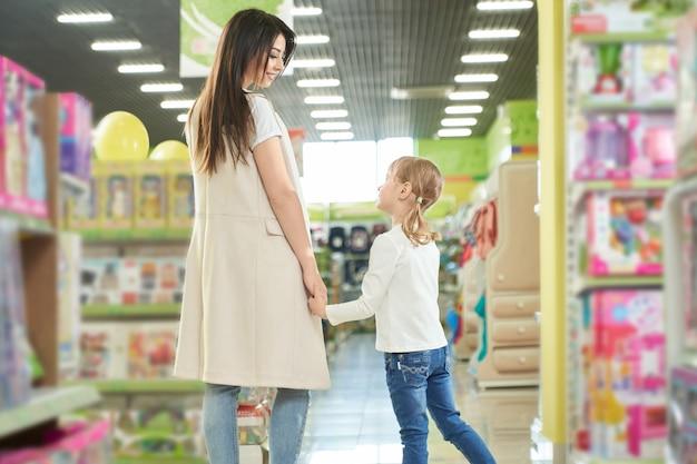 Feliz madre y niña caminando en el centro comercial, tienda de juguetes.