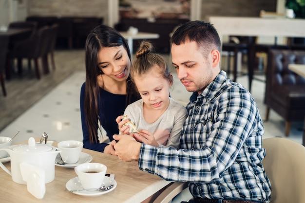 Feliz madre, padre y niña cenando tomando selfie con teléfono inteligente en el restaurante