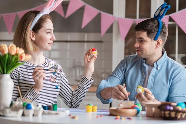 Feliz madre y padre pintando huevos juntos