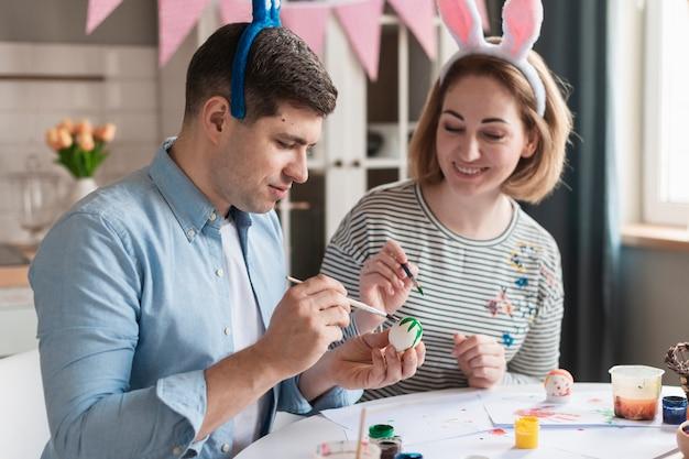 Feliz madre y padre pintando huevos de pascua