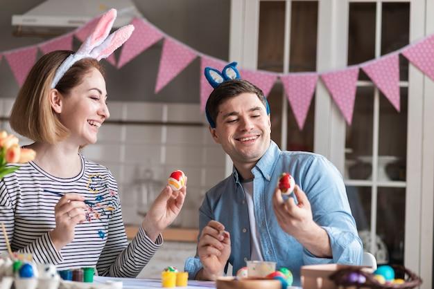 Feliz madre y padre pintando huevos para pascua
