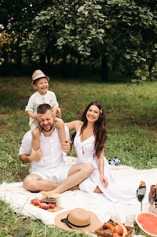 Feliz madre, padre y su lindo hijo pequeño haciendo un picnic en el parque de verano. niño sentado sobre los hombros de su padre. concepto de familia y ocio