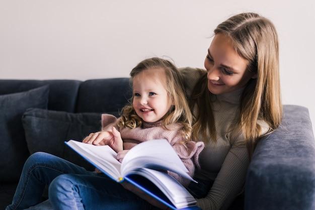 Feliz madre y pequeña hija leyendo libro, sentado en un cómodo sofá en la sala de estar