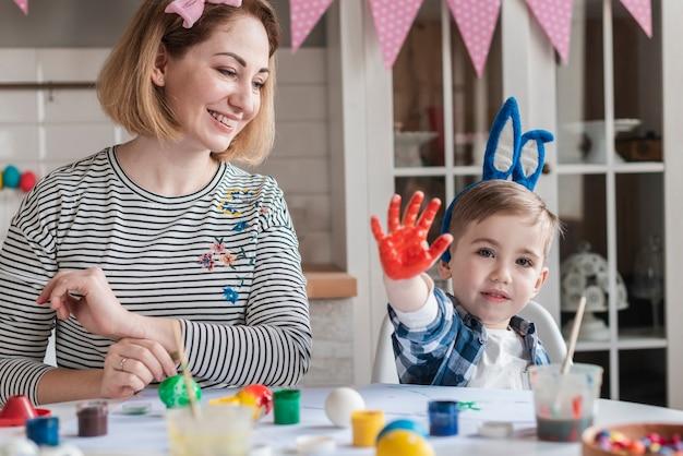 Feliz madre pintando huevos de pascua con hijo
