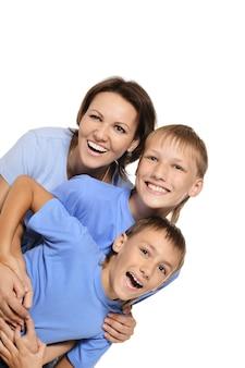 Feliz madre sonriente con sus hijos sobre un fondo blanco.