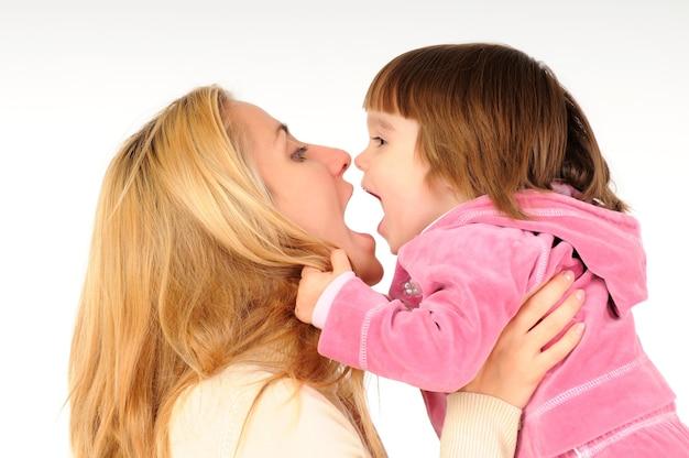 Feliz madre sosteniendo y jugando con su pequeña hija en ropa rosa sobre blanco