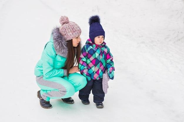 Feliz madre sosteniendo a la niña en el paseo en el bosque nevado de invierno