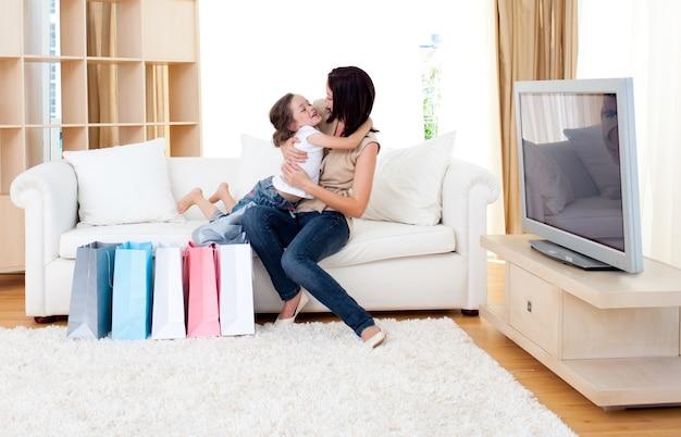 Feliz madre y su hija en casa después de ir de compras