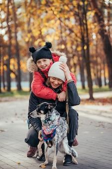 Feliz madre y su hija jugando con perro en el parque otoño