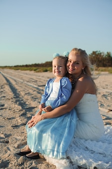 Feliz madre en el vestido de novia con su hija en la playa