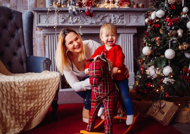 Feliz madre y niño encantador en el caballo de juguete posan ante un árbol de navidad