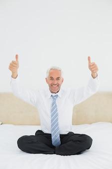 Feliz maduro empresario gesticular pulgares arriba en la cama