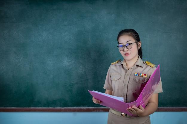 Feliz maestro tailandés en traje oficial actuando delante del tablero