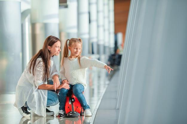 Feliz mamá y niña con tarjeta de embarque en el aeropuerto