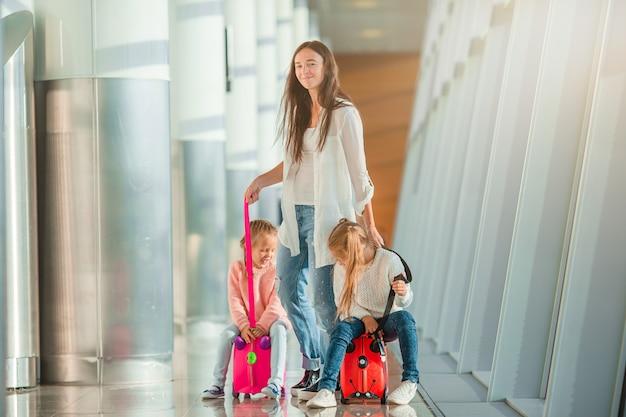 Feliz mamá y niñas con tarjeta de embarque en el aeropuerto