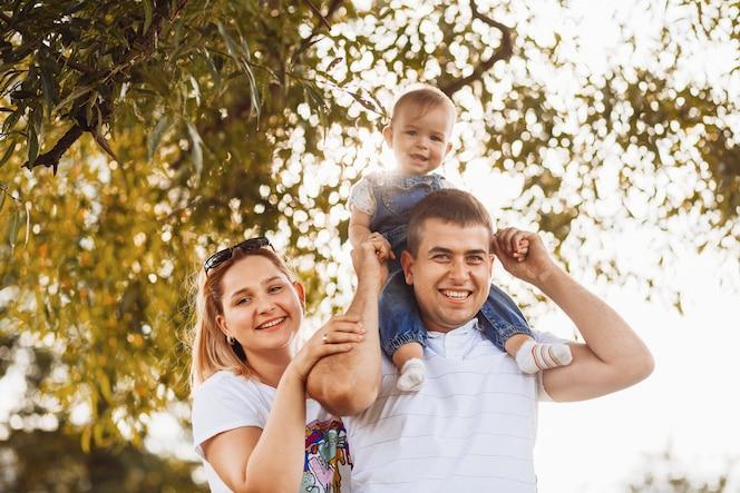 Feliz mamá papá mantenga pequeña hija en sus brazos de pie en los rayos del sol de la tarde