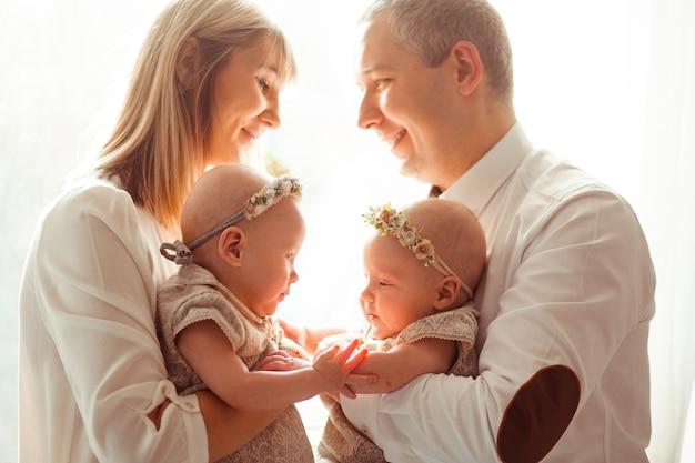 Feliz mamá y papá posan con divertidos gemelos en sus brazos ante una ventana brillante