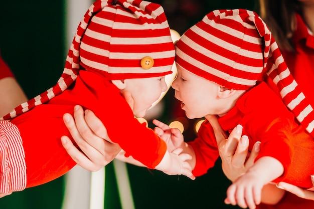 Feliz mamá y papá posan con graciosos gemelos en sus brazos