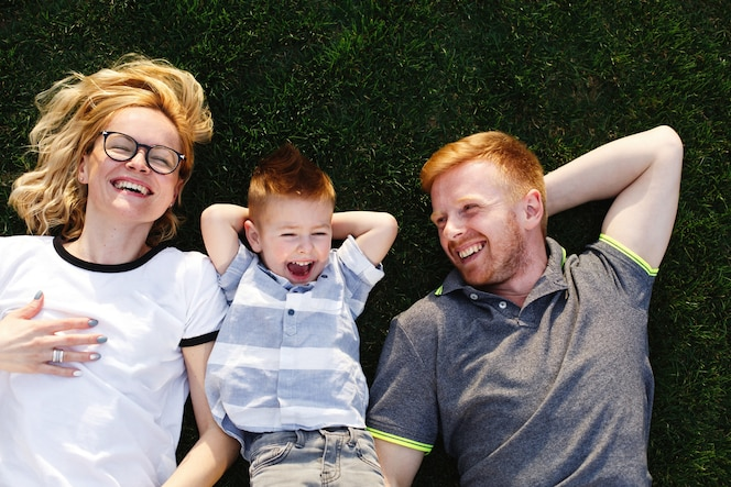 Feliz mamá, papá y su pequeño hijo se encuentran en la hierba verde