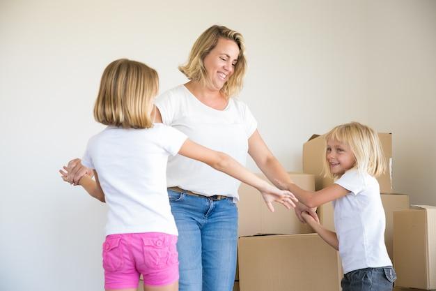 Feliz mamá rubia caucásica y dos chicas bailando en la habitación entre cajas de cartón