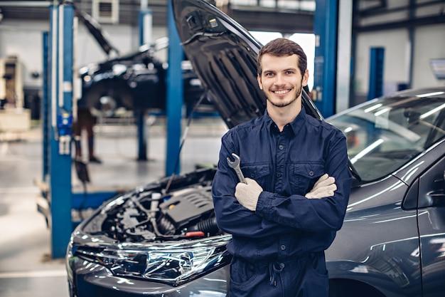 Feliz mecánico de pie junto al auto