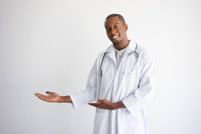 Feliz médico masculino negro apuntando al espacio vacío y presentar el producto.