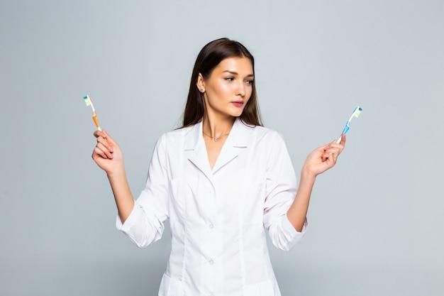 Feliz médico mujer sosteniendo cepillos de dientes aislados en la pared blanca