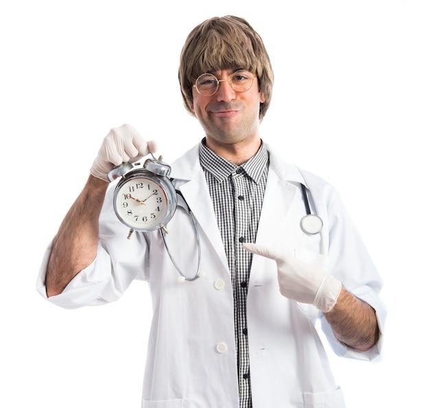 Feliz médico sosteniendo el reloj de la vendimia