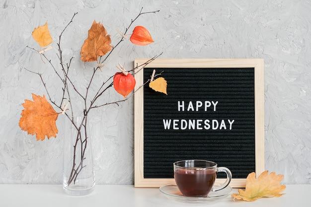Feliz miércoles texto en pizarra negra y ramo de ramas con hojas amarillas en pinzas para la ropa en un jarrón sobre la mesa