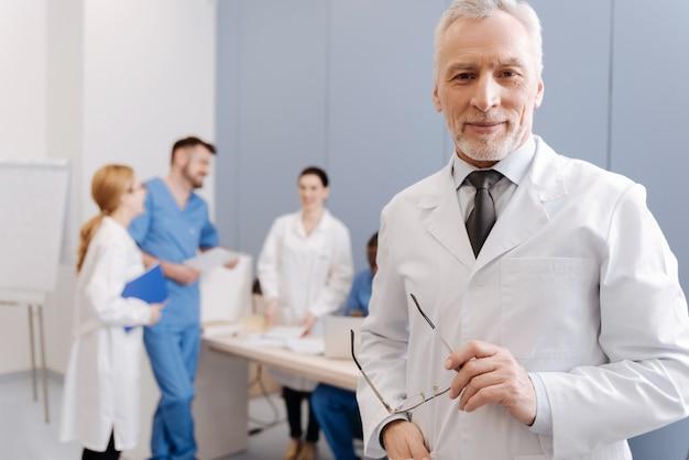 Feliz de mis responsabilidades laborales. carismático guapo médico anciano sonriendo y teniendo la conferencia en la clínica mientras los estudiantes disfrutan de la conversación