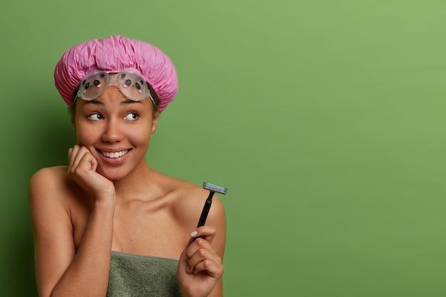 Feliz modelo de piel oscura que va a afeitarse sostiene una maquinilla de afeitar, usa una toalla de baño y un gorro impermeable, tiene dientes blancos perfectos, piensa en algo agradable, aislado en una pared verde, copie el espacio a un lado para promo