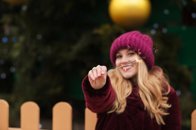 Feliz modelo rubia sosteniendo brillantes luces de bengala en el árbol de navidad principal en kiev. efecto de desenfoque