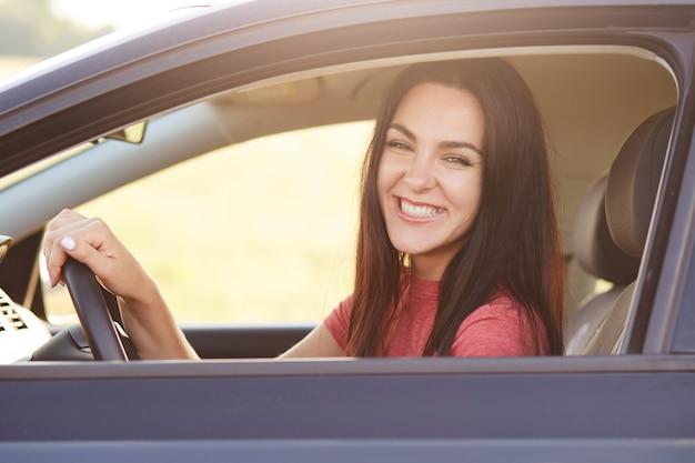 Feliz morena mujer conductora con amplia sonrisa