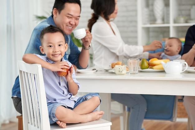 Feliz muchacho asiático en el desayuno con la familia