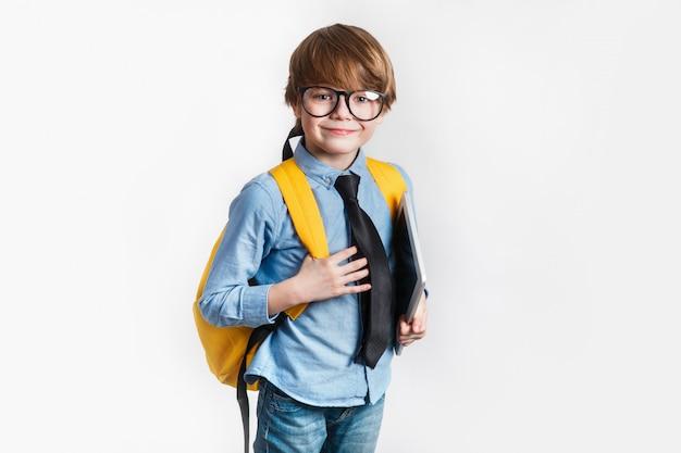 Feliz muchacho inteligente lindo en vasos con mochila y tableta en la mano. de vuelta a la escuela.